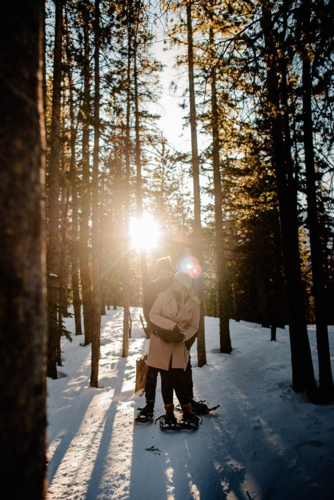 couple snuggling in trees with snow shoes on