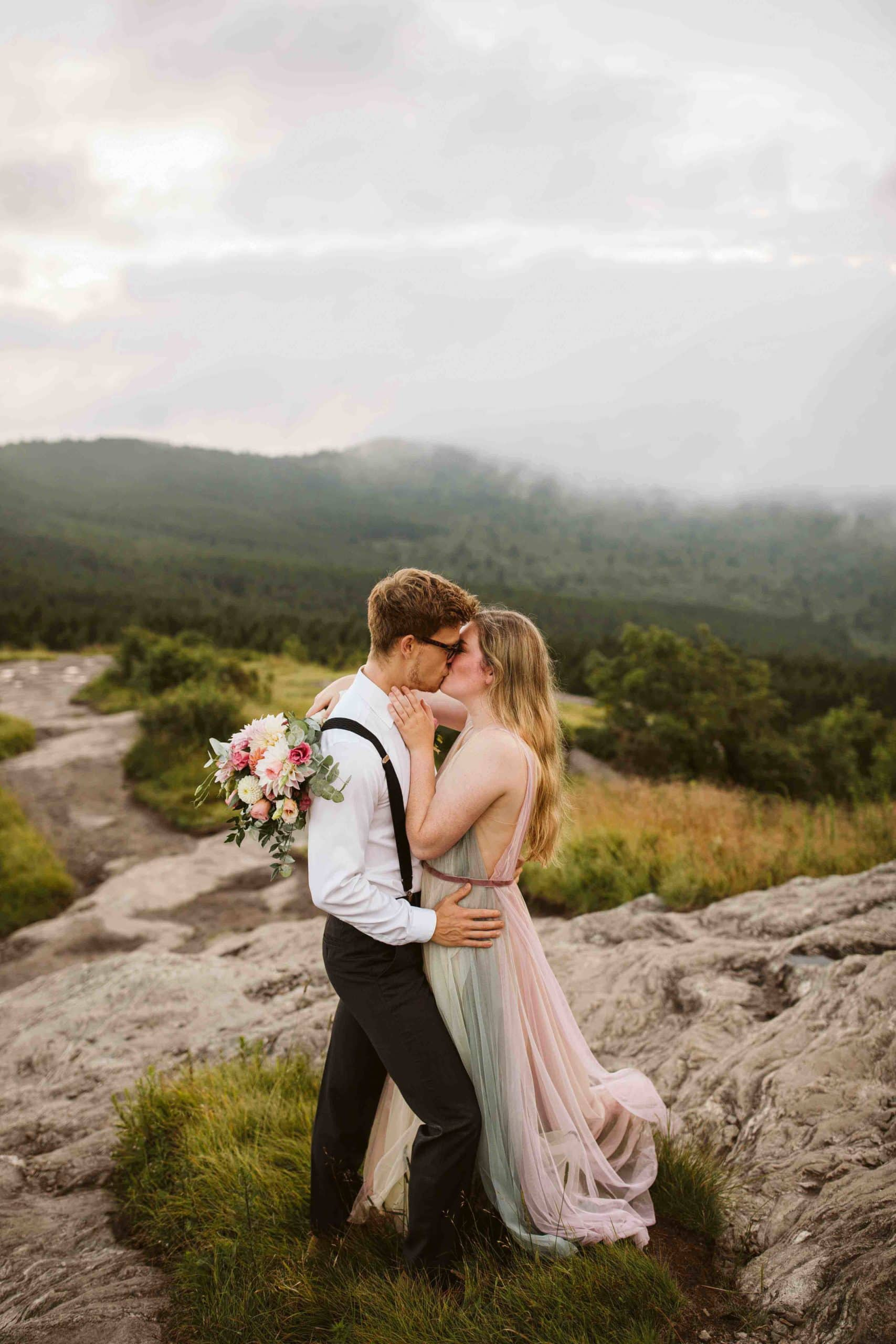 couple on edge of cliff with moody skies in the background content because they discovered one of the best places to elope
