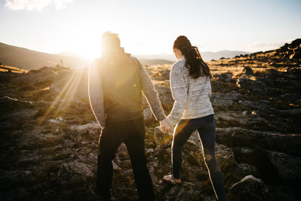 couple walking away into the sunset on top of a mountain