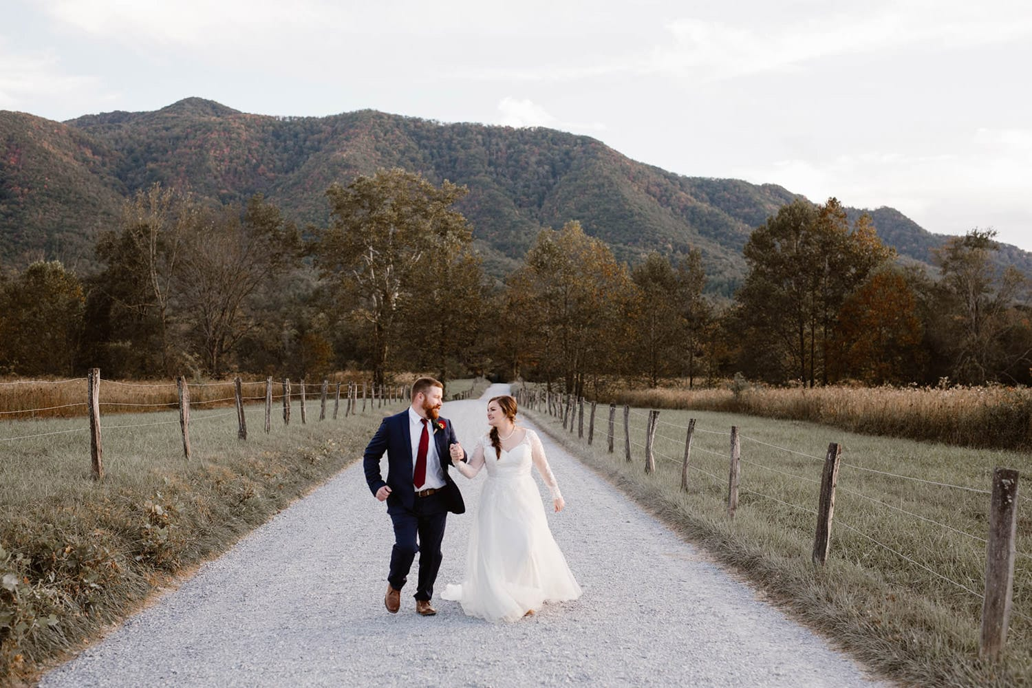 couple in a dirt road with the mountains behind them