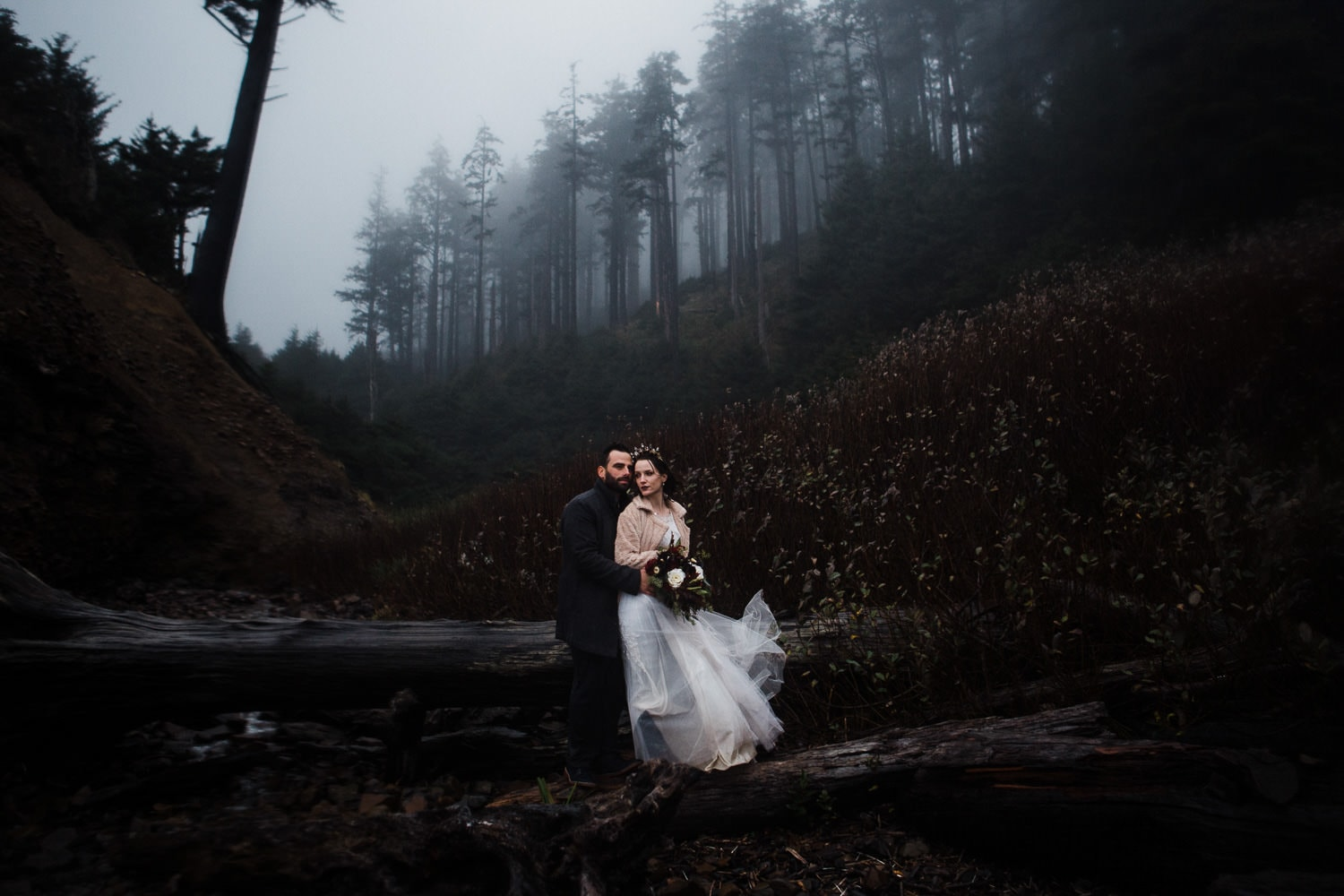 couple near the beach with forest hillside behind them
