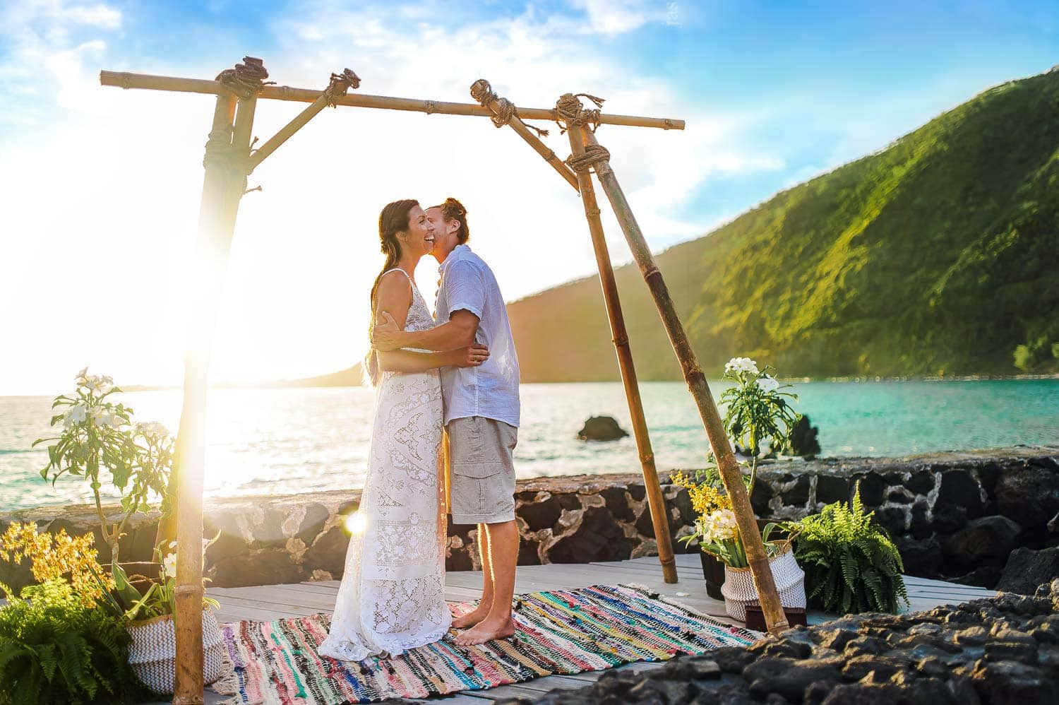 couple standing under ceremony site on beach side