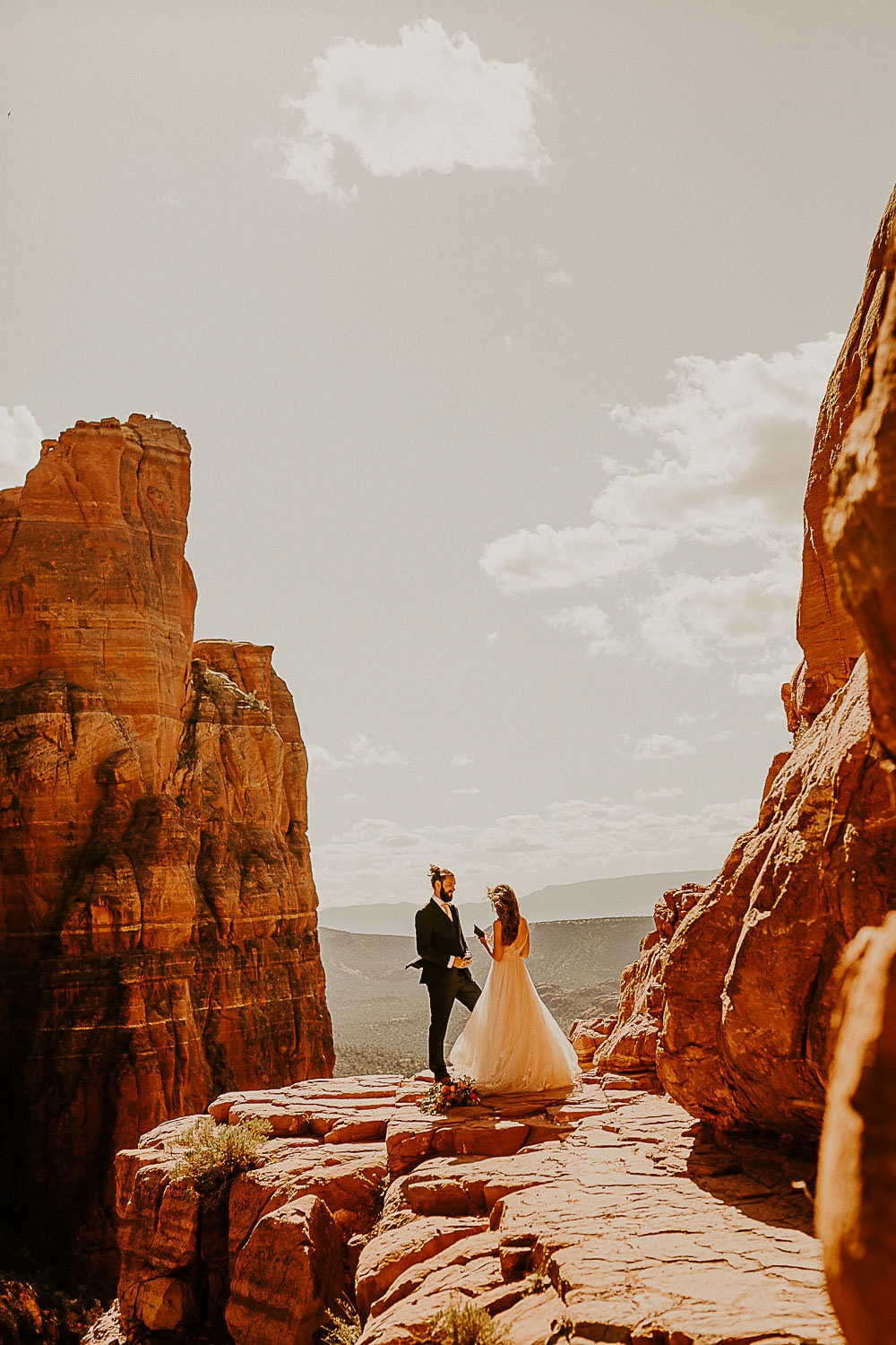 couple standing by cliffs happy because they decided on the best places to elope