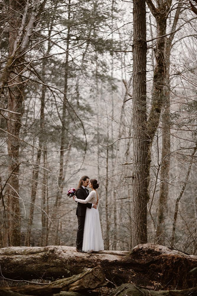 couples standing in forest content because they decided on the best places to elope