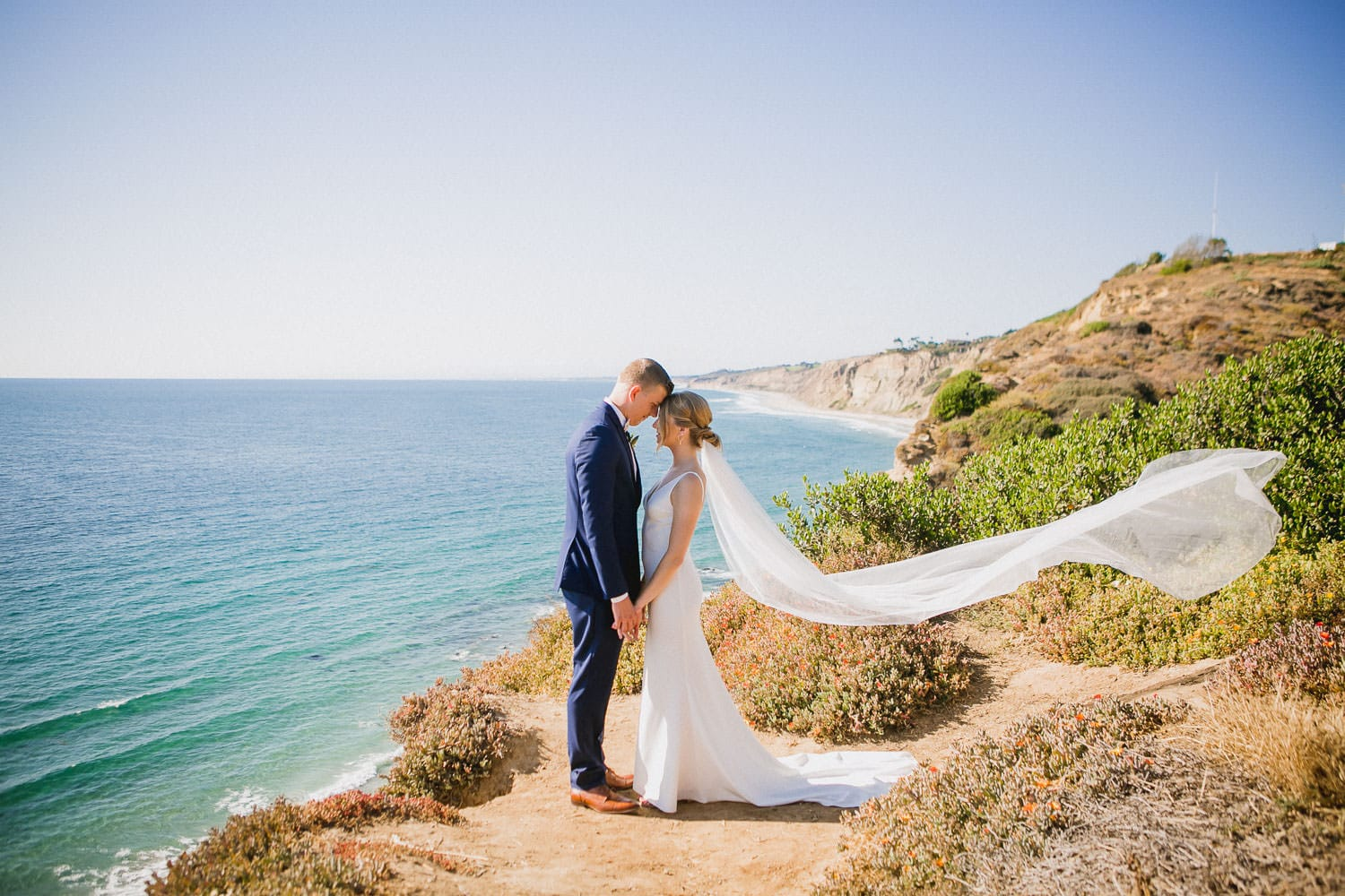 couples standing on cliff edge near ocean happy because they decided on the best places to elope
