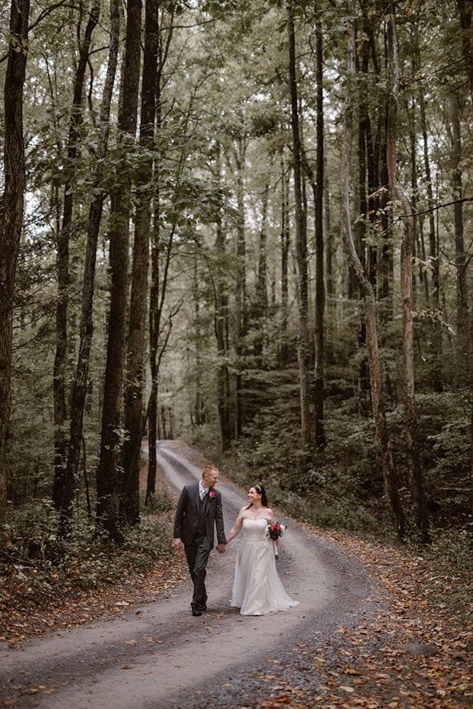 couple in road on a forest trial happy because because they decided on the best places to elope