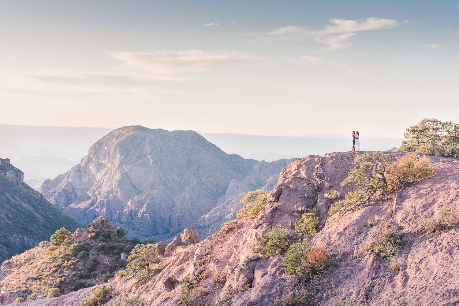 couple on a cliff edge with the horizon in the background content because because they decided on the best places to elope