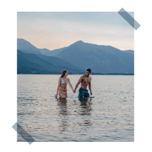 couple holding hands in alpine lake