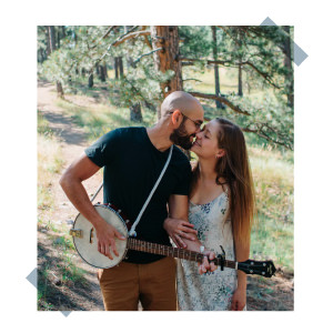 couple kissing in the colorado trees while celebrating anniversary playing banjo