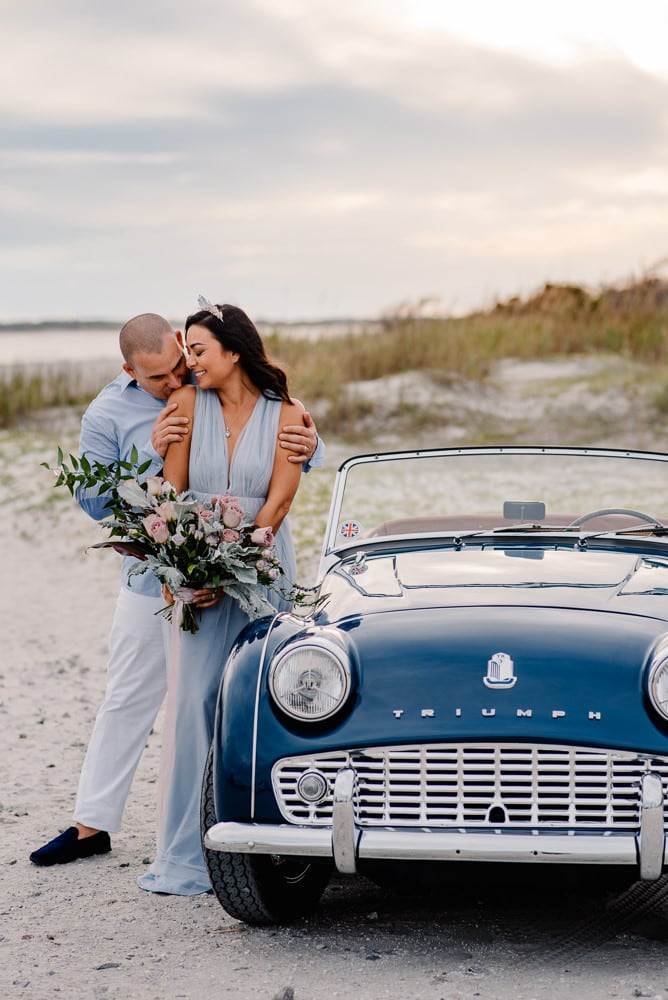 Couple dressed up in formal clothes on a beach near a vintage blue car