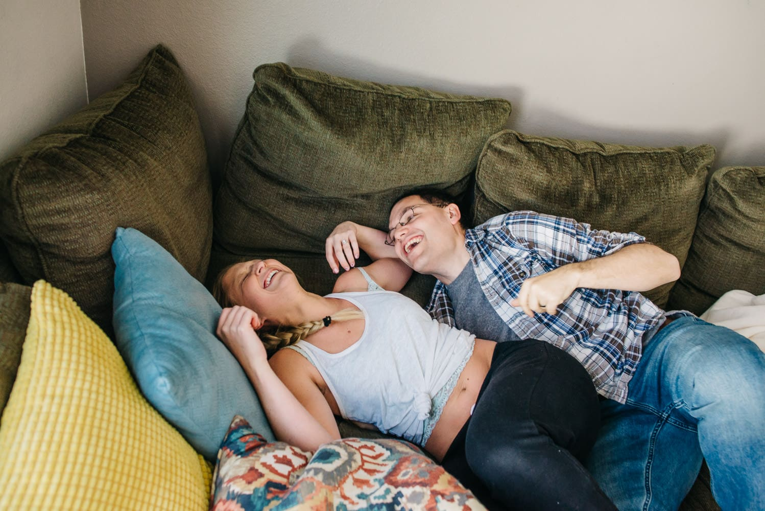 Couple laughing snuggling on couch