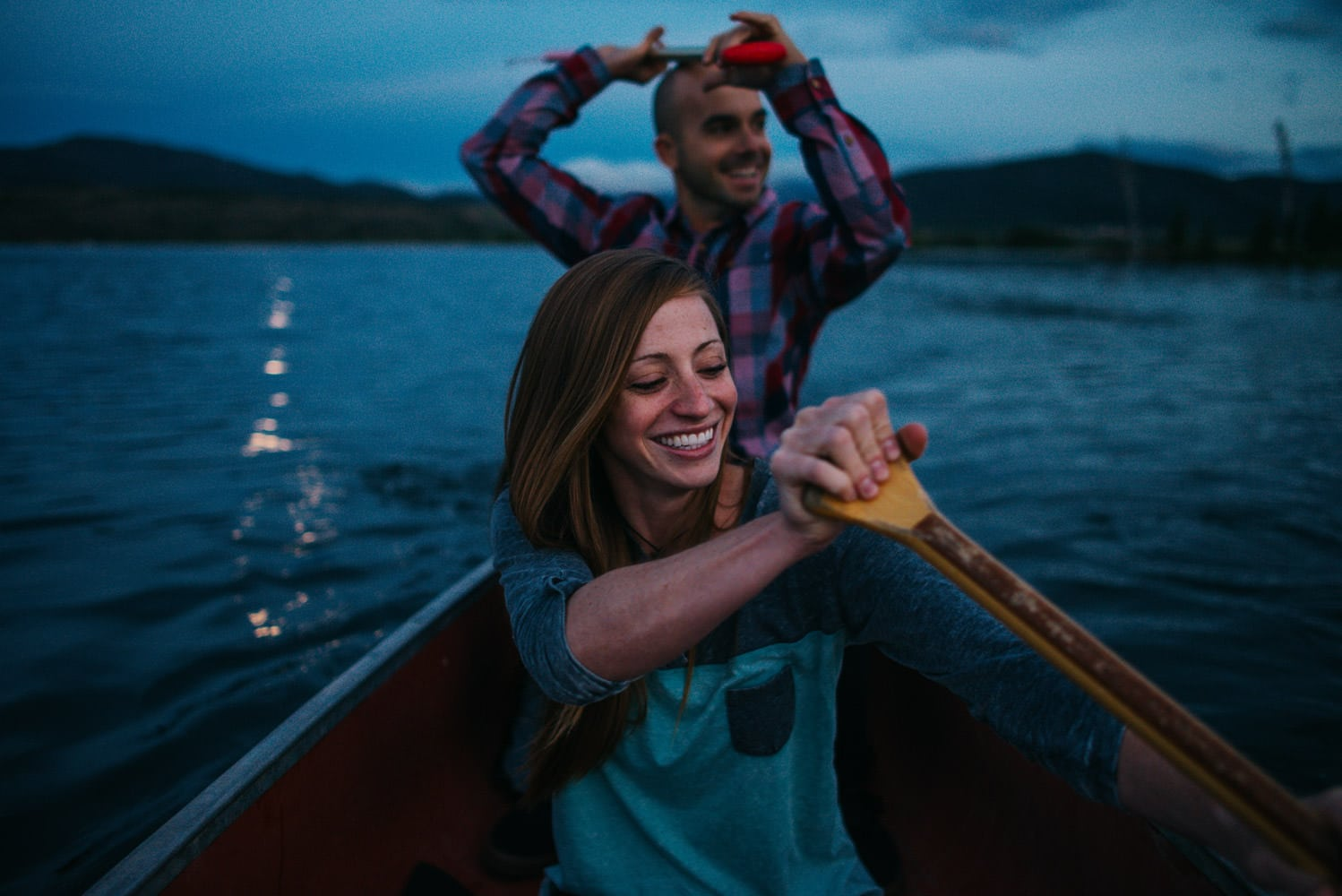 Couple in a canoe after sunset laughing