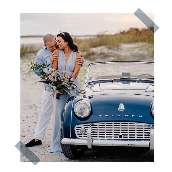 couple near a vintage car on a beach
