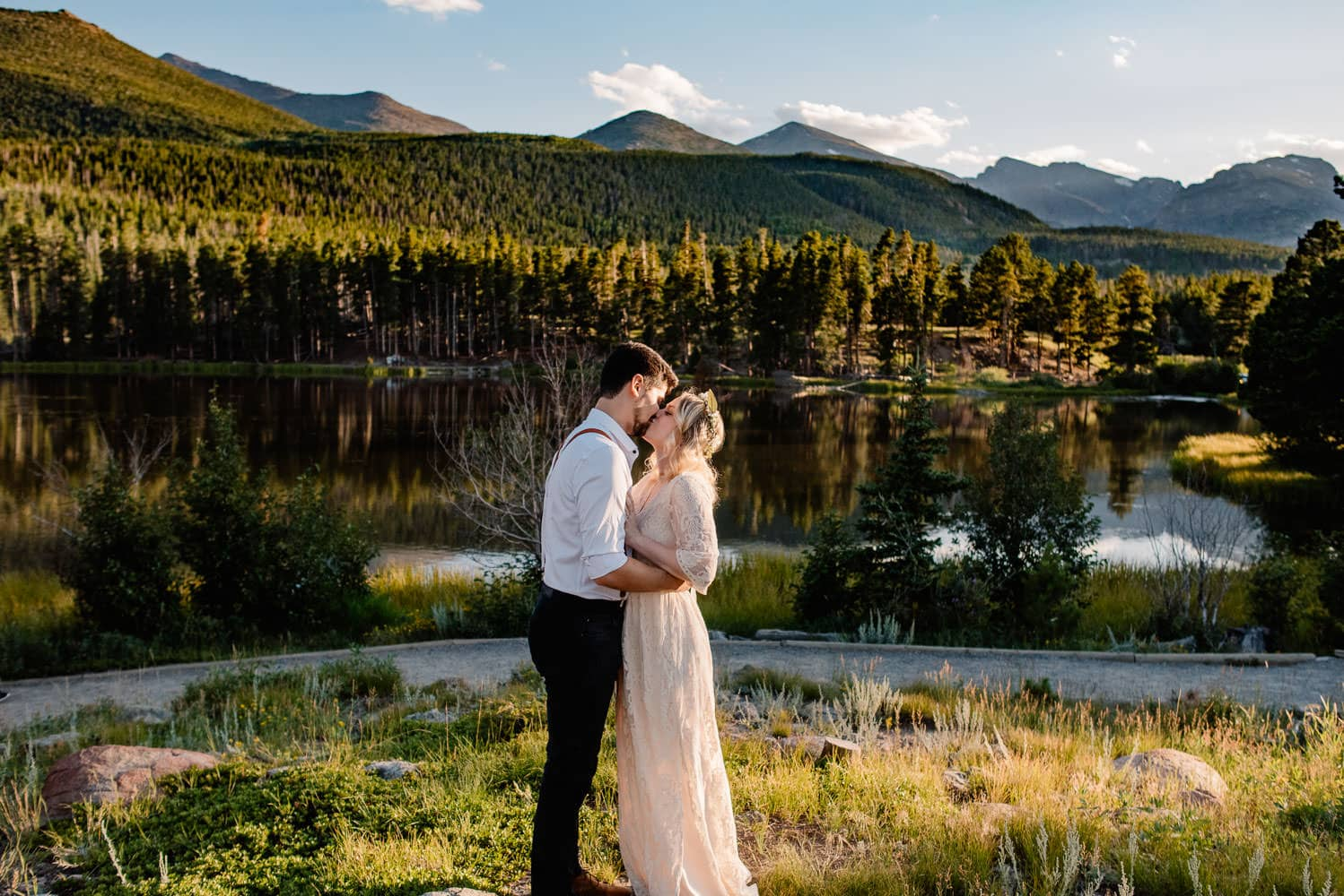 couple holding hands at their sprague lake wedding in rocky mountain national park near sunset