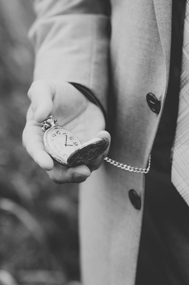 groom holding pocket watch
