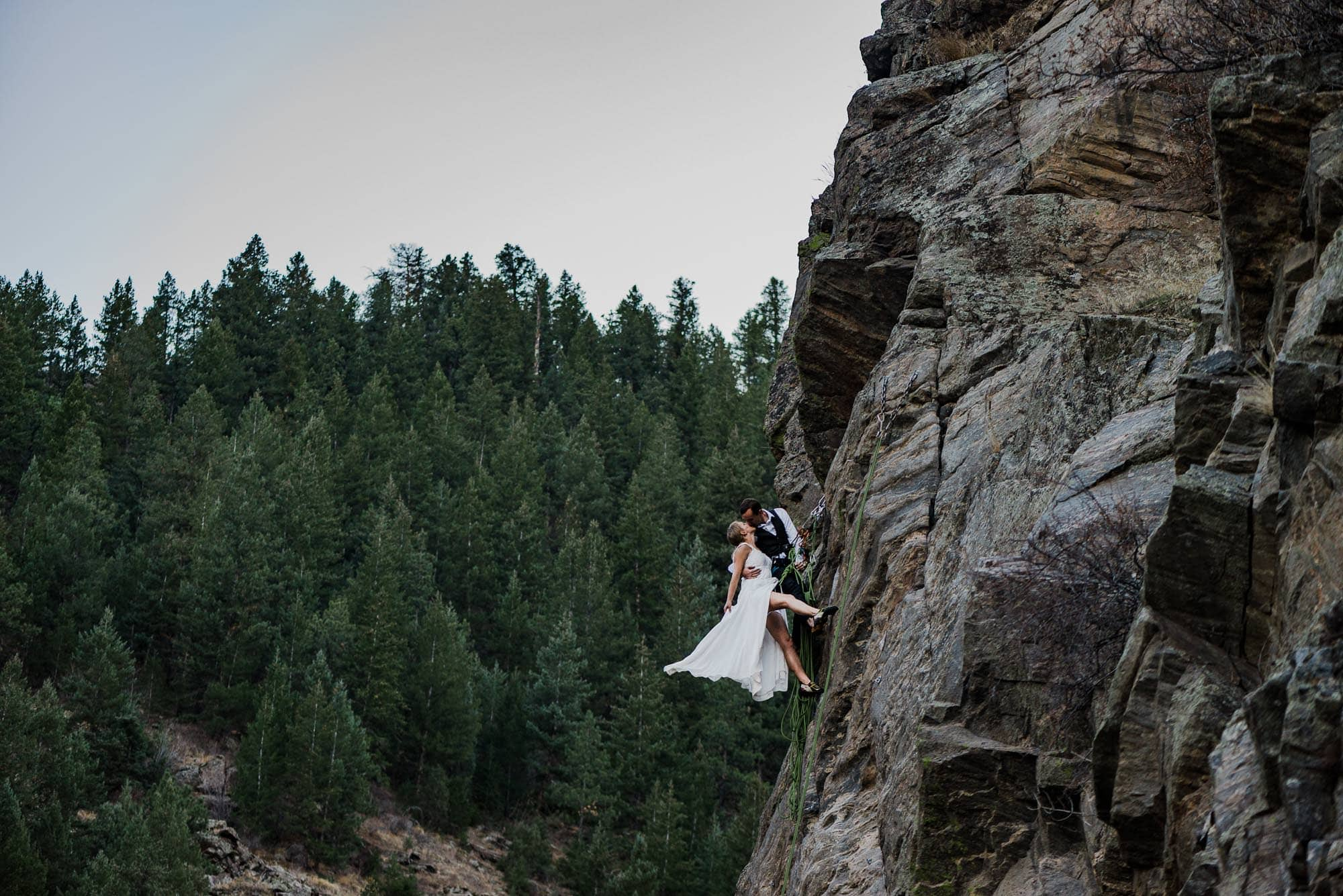 Eloping couple getting married on the side of a cliff face while rock climbing
