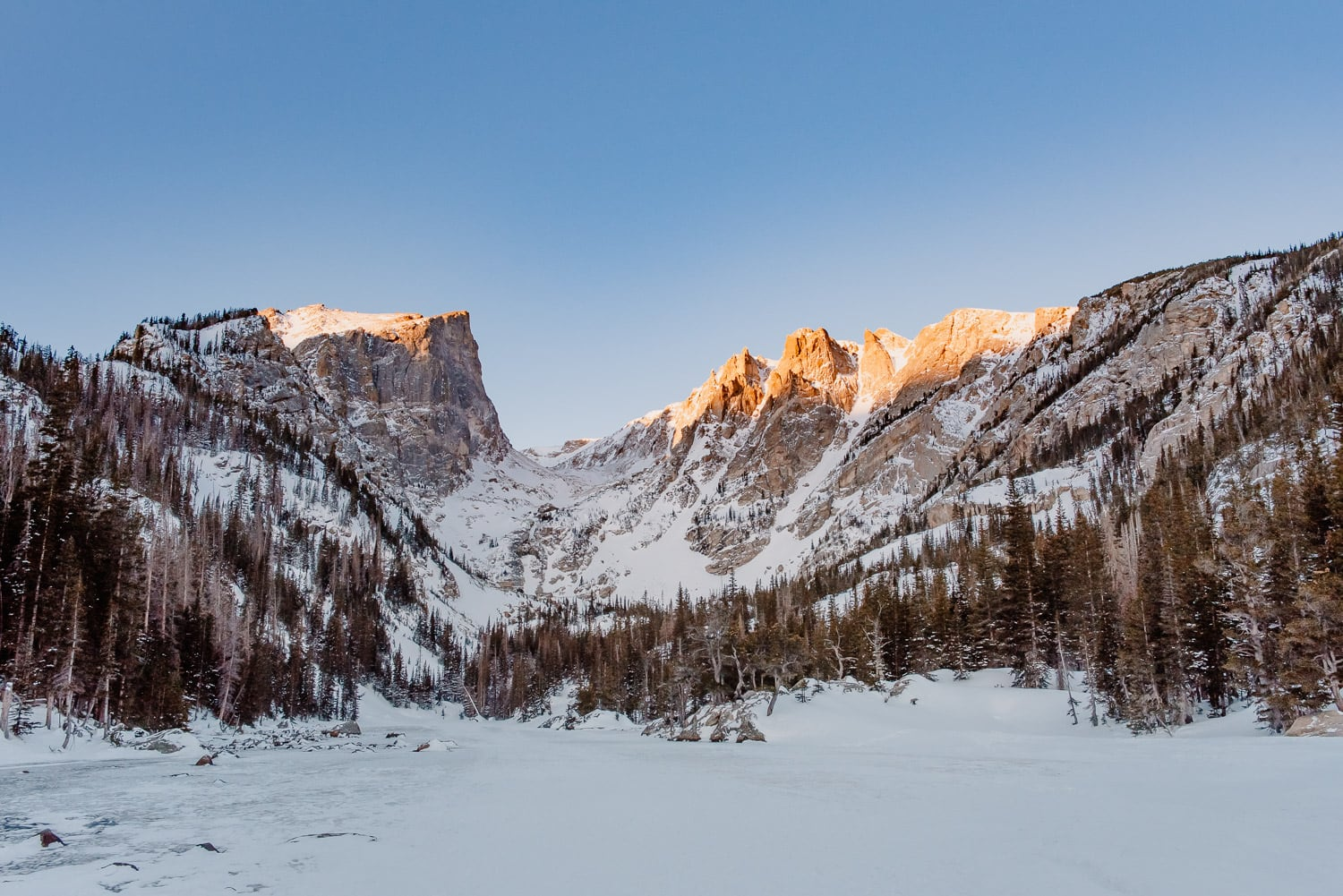 Dream lake Colorado photo of an alpine lake in the middle of winter as the sun comes up creating an alpine glow