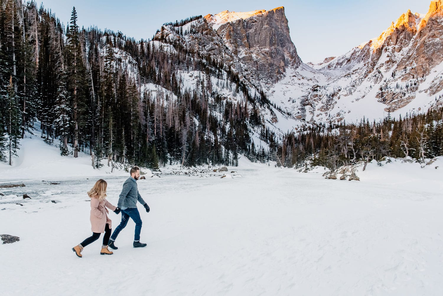 couple running at Dream Lake Colorado during winter.