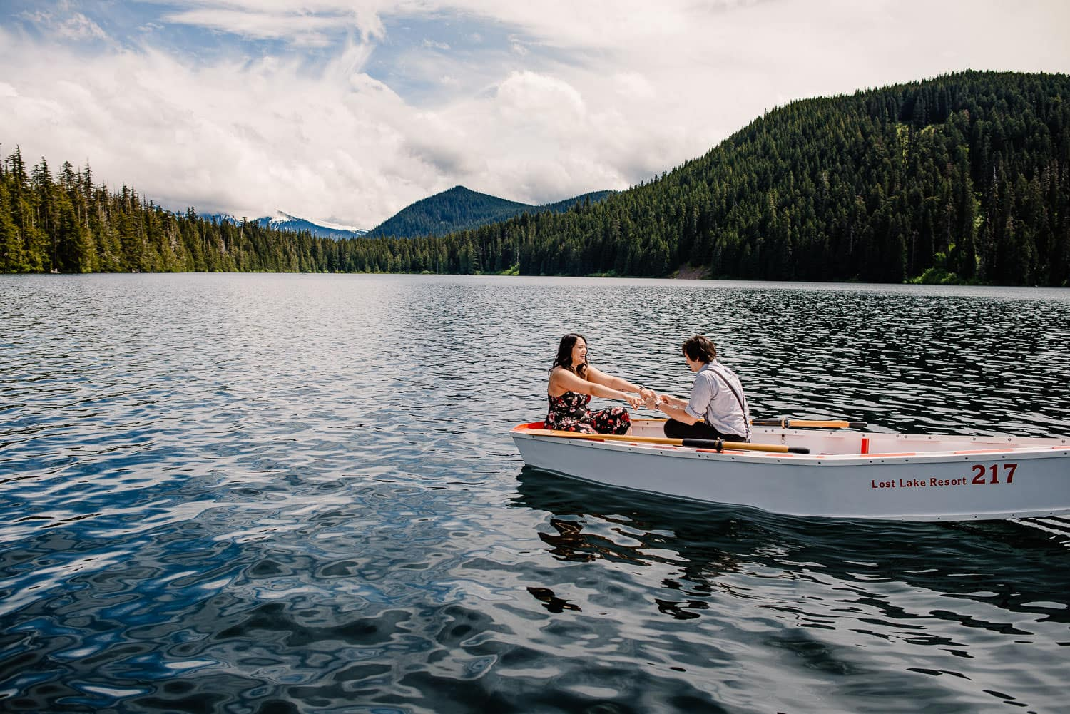 Couple in a boat rowing on an alpine lake