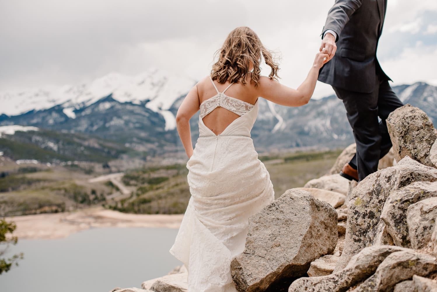 bride in her elopement wedding dress walking up rocks in mountains while holding her spouses hand.