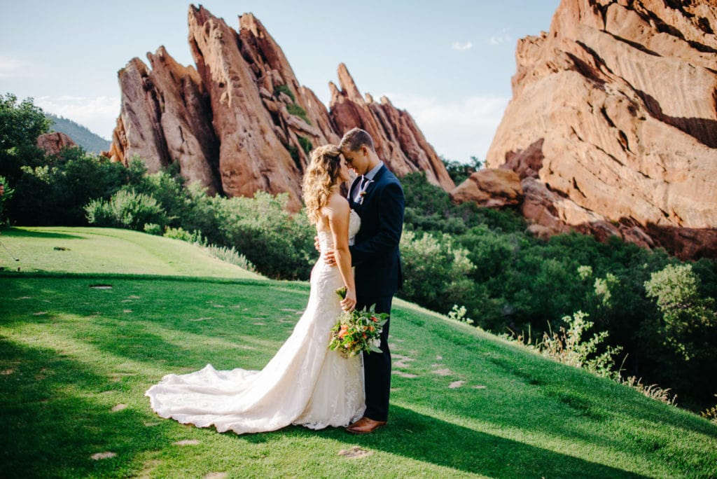 bride in trumpet wedding dress on a green grass and red rocks area