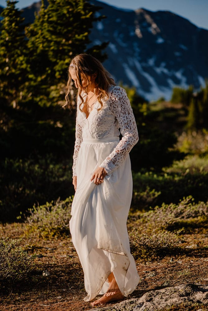 bride walking in the mountains barefoot as her elopement wedding dress gets dirty