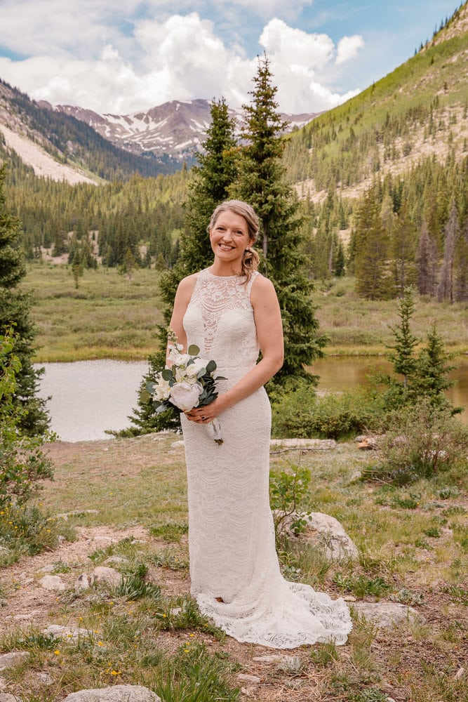 bride in her column style elopement wedding dress in the mountains smiling holding her flowers