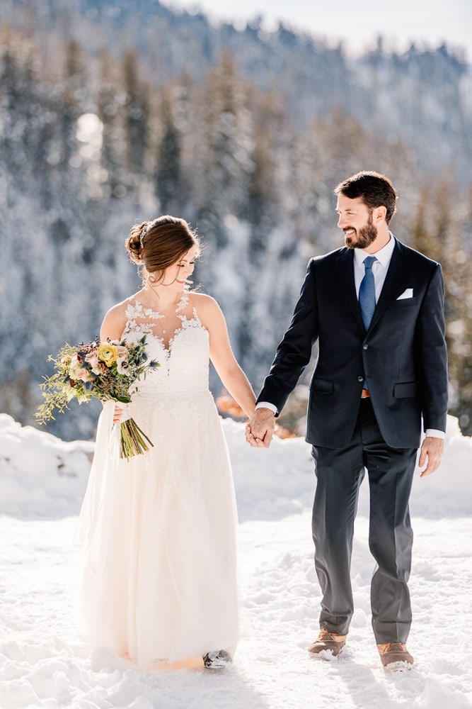 bride in the snow in her winter wedding dress on her elopement wedding day
