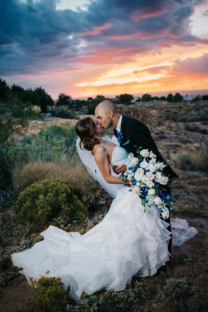 bride in textured elopement wedding dress at sunset kissing her new spouse as the colors make the sky glow bright.
