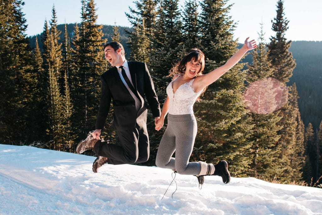 bride and groom jumping in the snow as bride wears a two piece wedding dress without the bottom on yet.