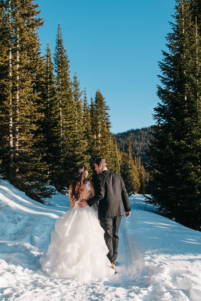 bride and groom walking away in the snow as she wears her two piece elopement wedding dress