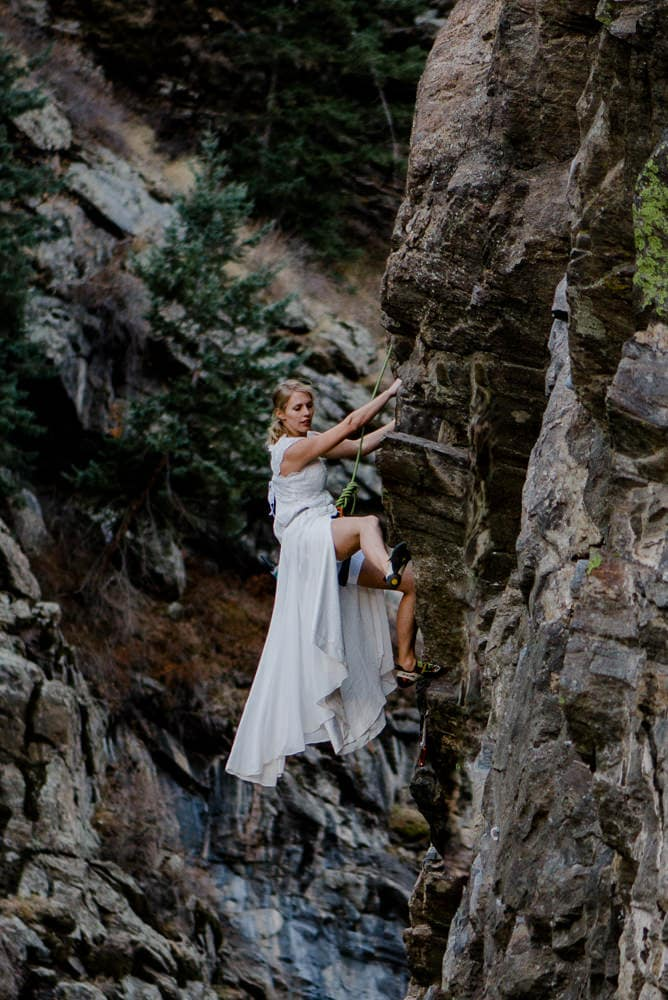 bride rock climbing in her altered wedding dress