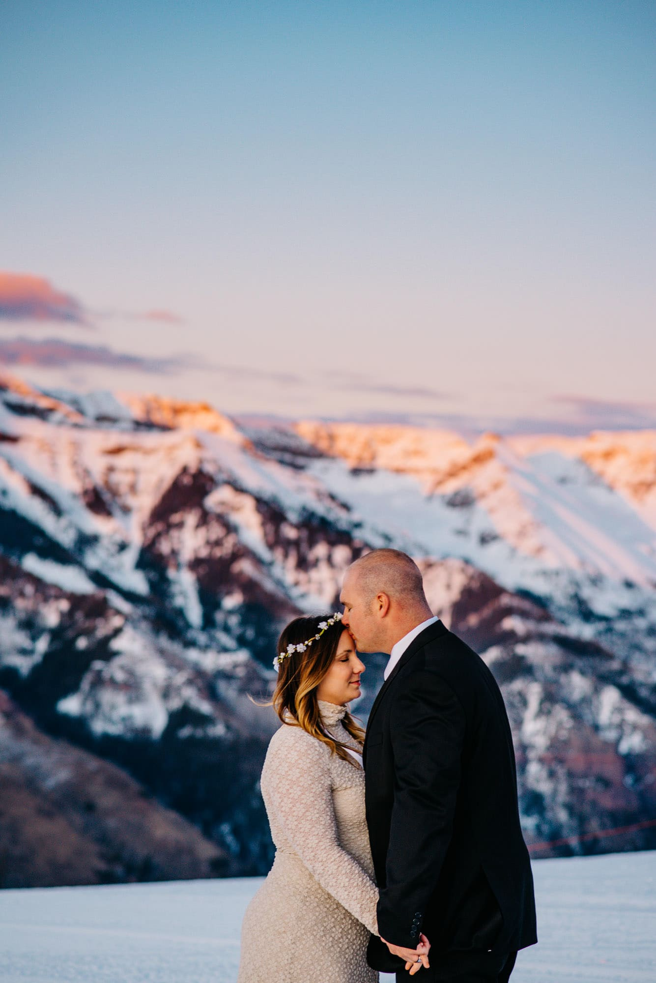 groom kissing brides head on top of a mountain in the snow as the sun glows behind them on the mountains
