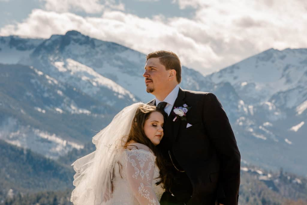 couple having a rocky mountain national park wedding snugging in front of the mountains