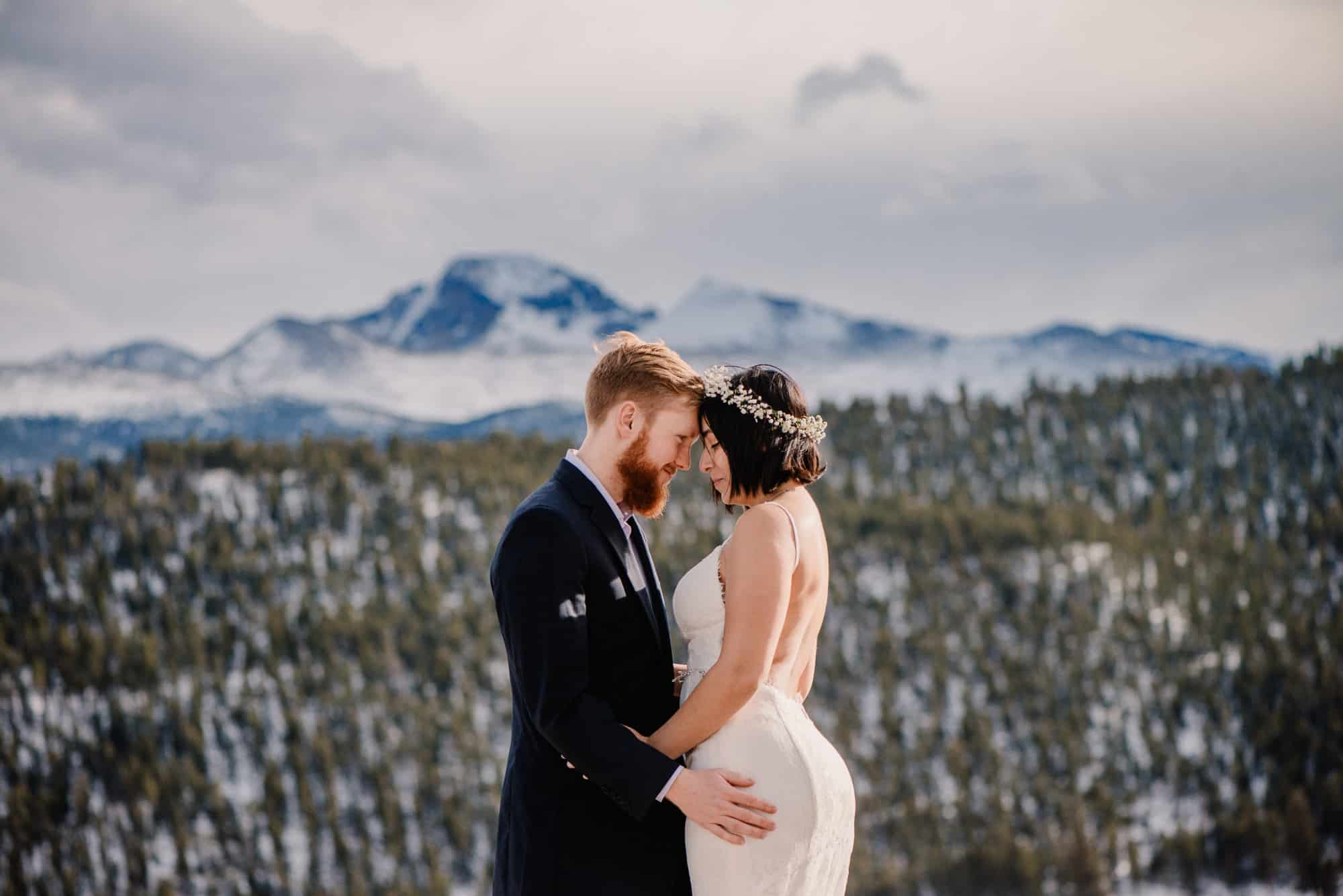 coupe having a rocky mountain national park wedding cuddling with mountains in the background