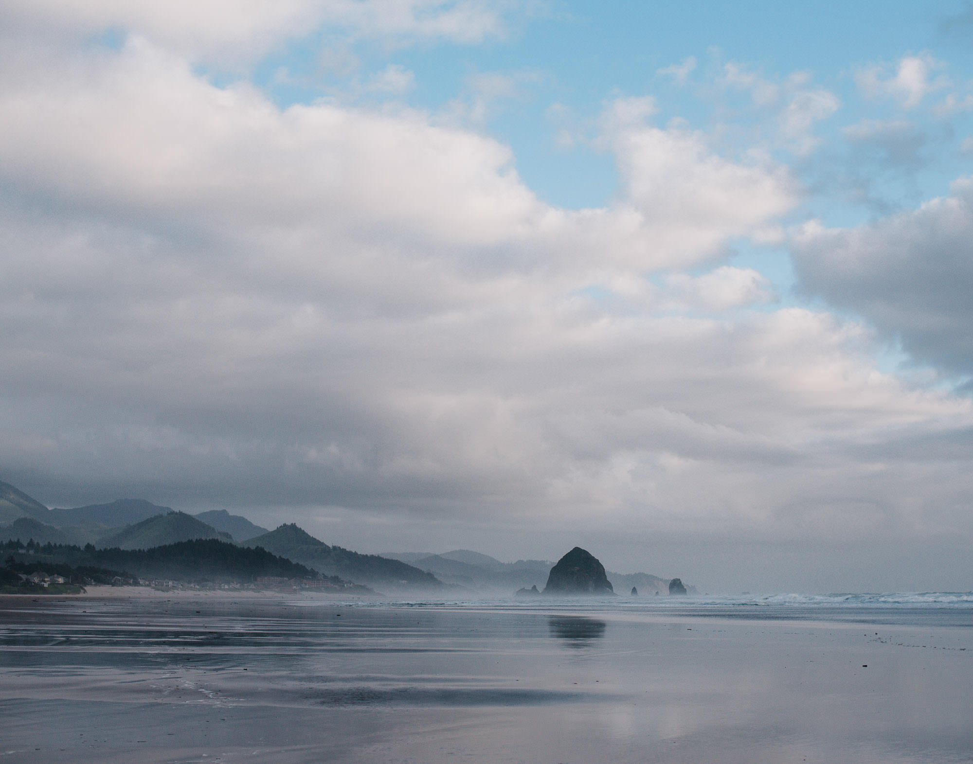 view of the beach in Oregon with the water reflecting the sky and mountains in the background