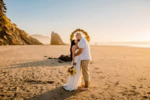 couple standing on beaching having a cannon beach elopement as the sunsets behind them with sea rocks in the distance
