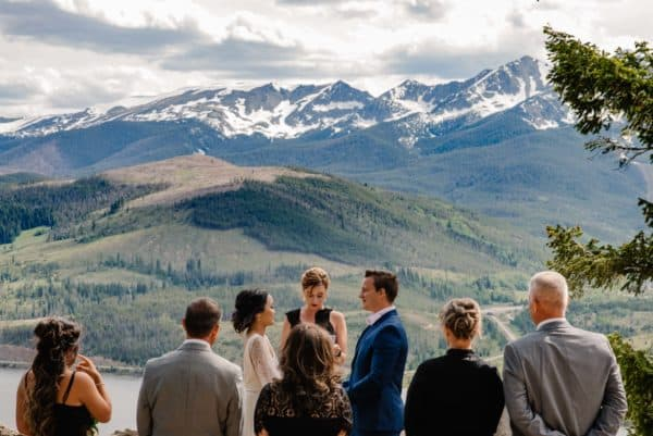 small Breckenridge elopement location at sapphire point guests standing around bride and groom overlooking the mountains into Breckenridge.
