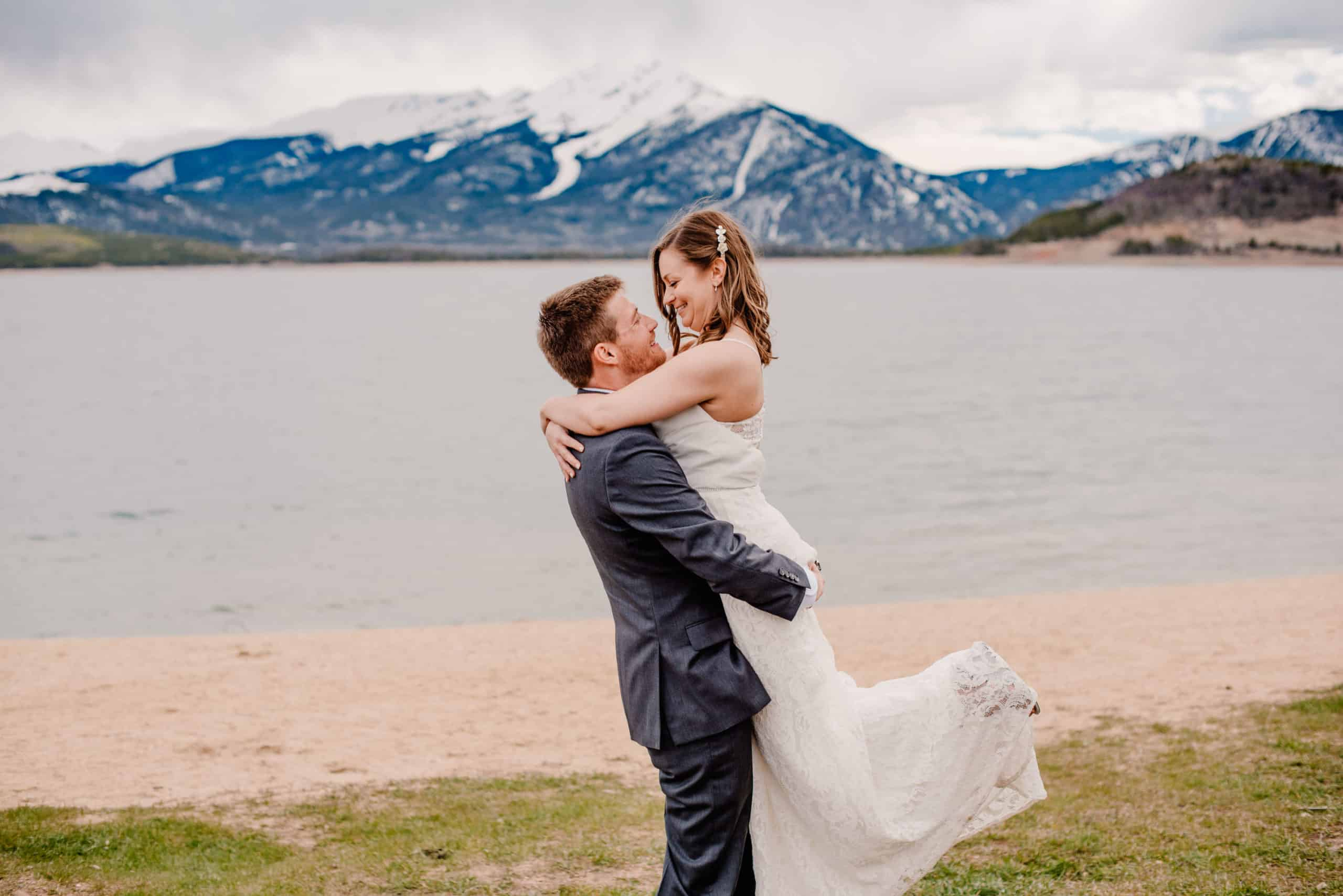 Groom lifting up bride near water front with mountains in the background