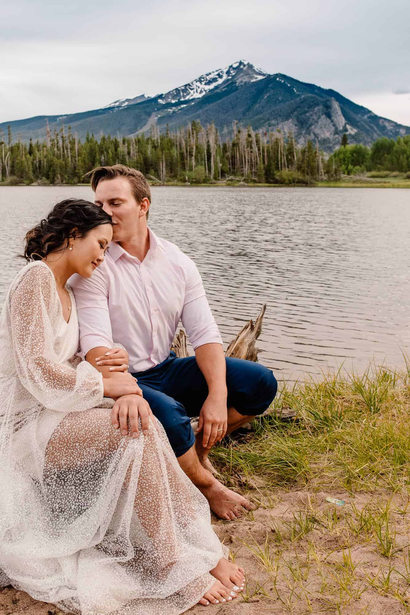 couple sitting on a log by the alpine lake, groom kissing bride on the forehead