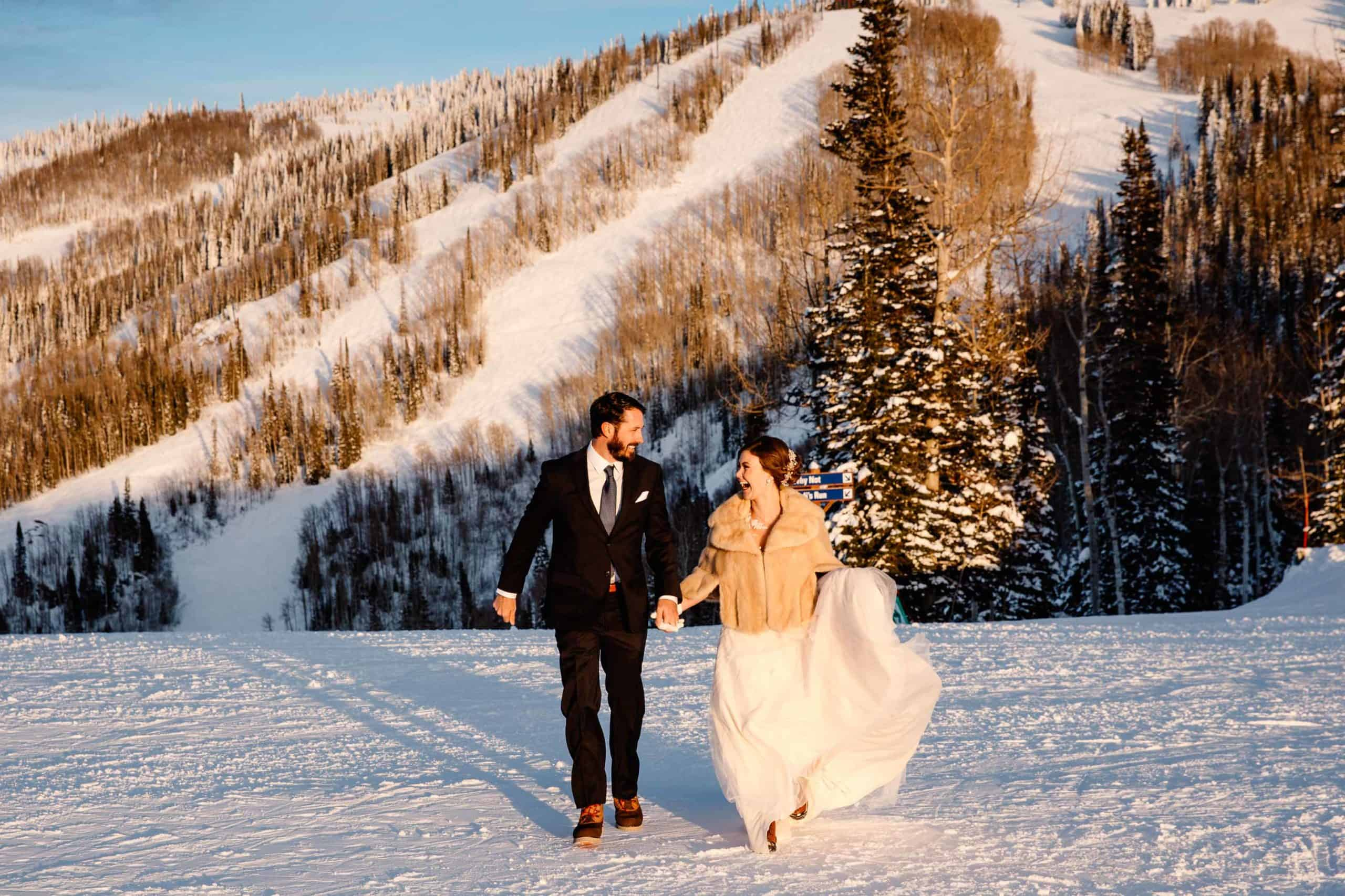 couple laughing as they hold hands on a ski resort hill after their wedding ceremony