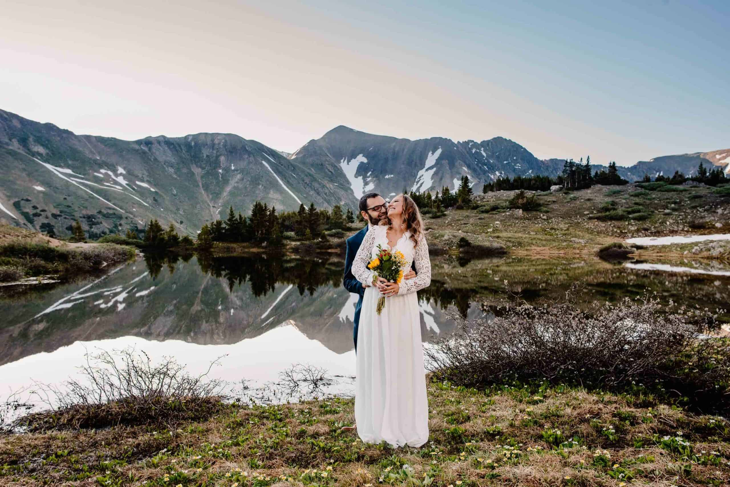 groom standing behind bride wrapping his arms around her kissing her cheek as they stand near an alpine lake with sweeping mountain views