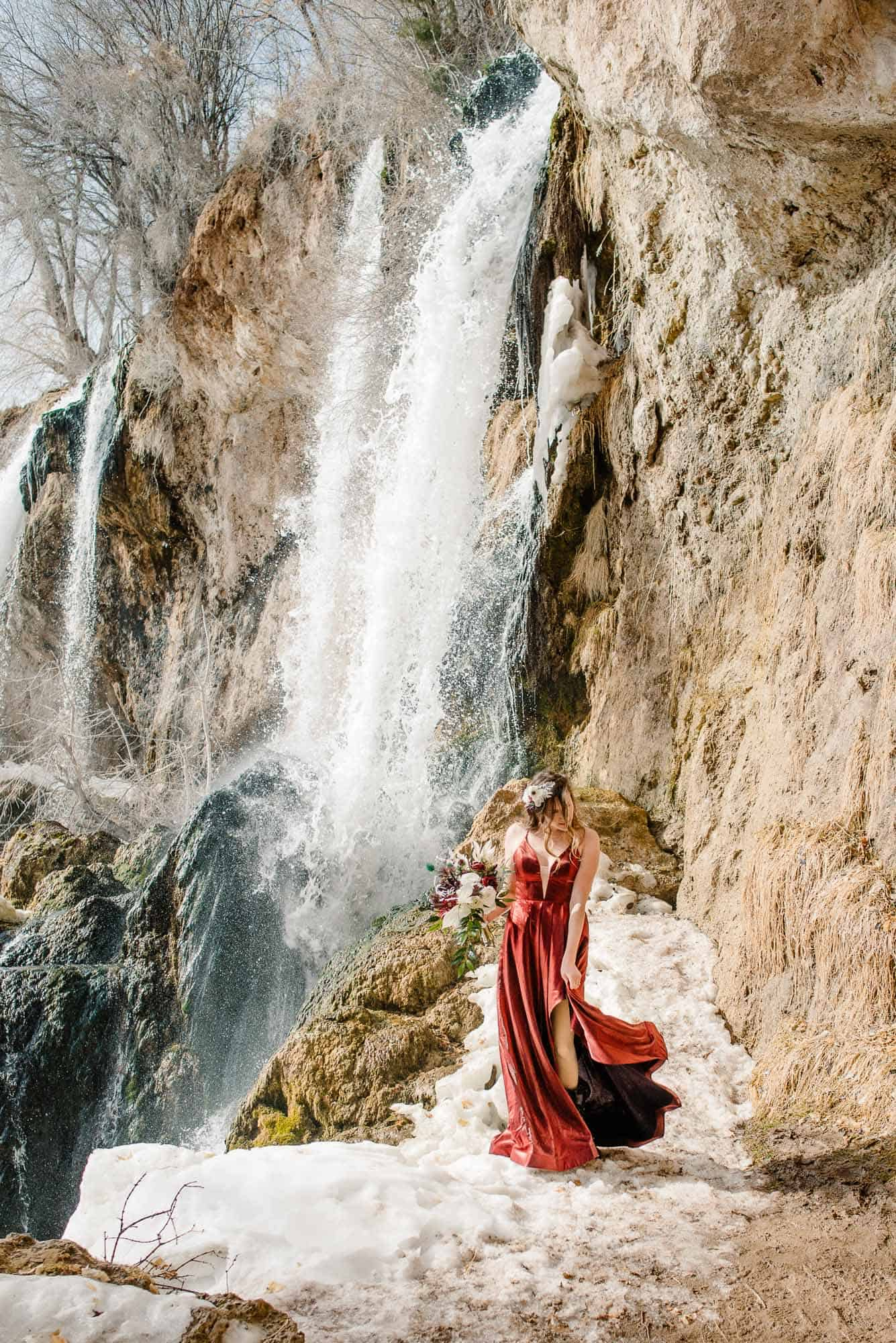 bride in a red dress holding her dress down as she twirls near a waterfall