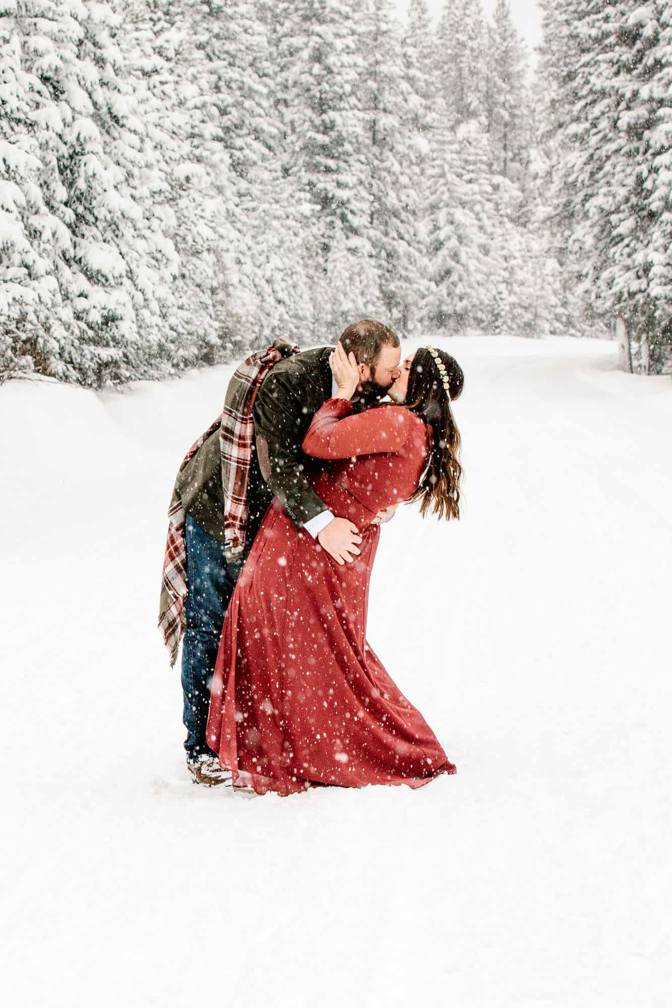 couple doing a dip kiss in the snow as snow falls all around them and trees are coated with snow in the background