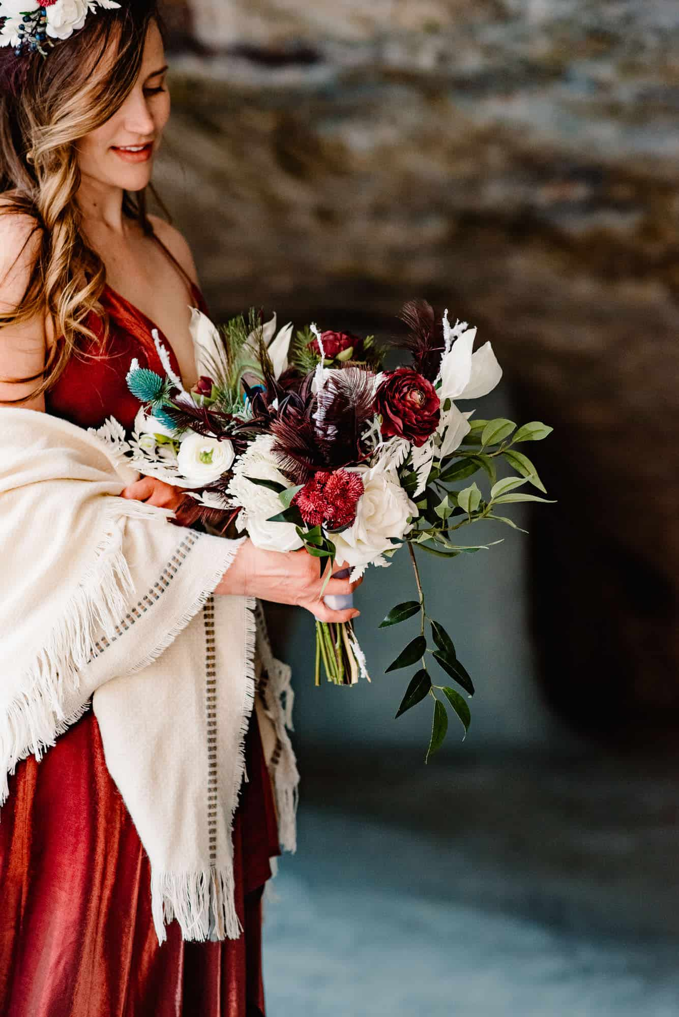 bride in a red dress holding flowers covering her arms with a shawl to stay warm in the winter.