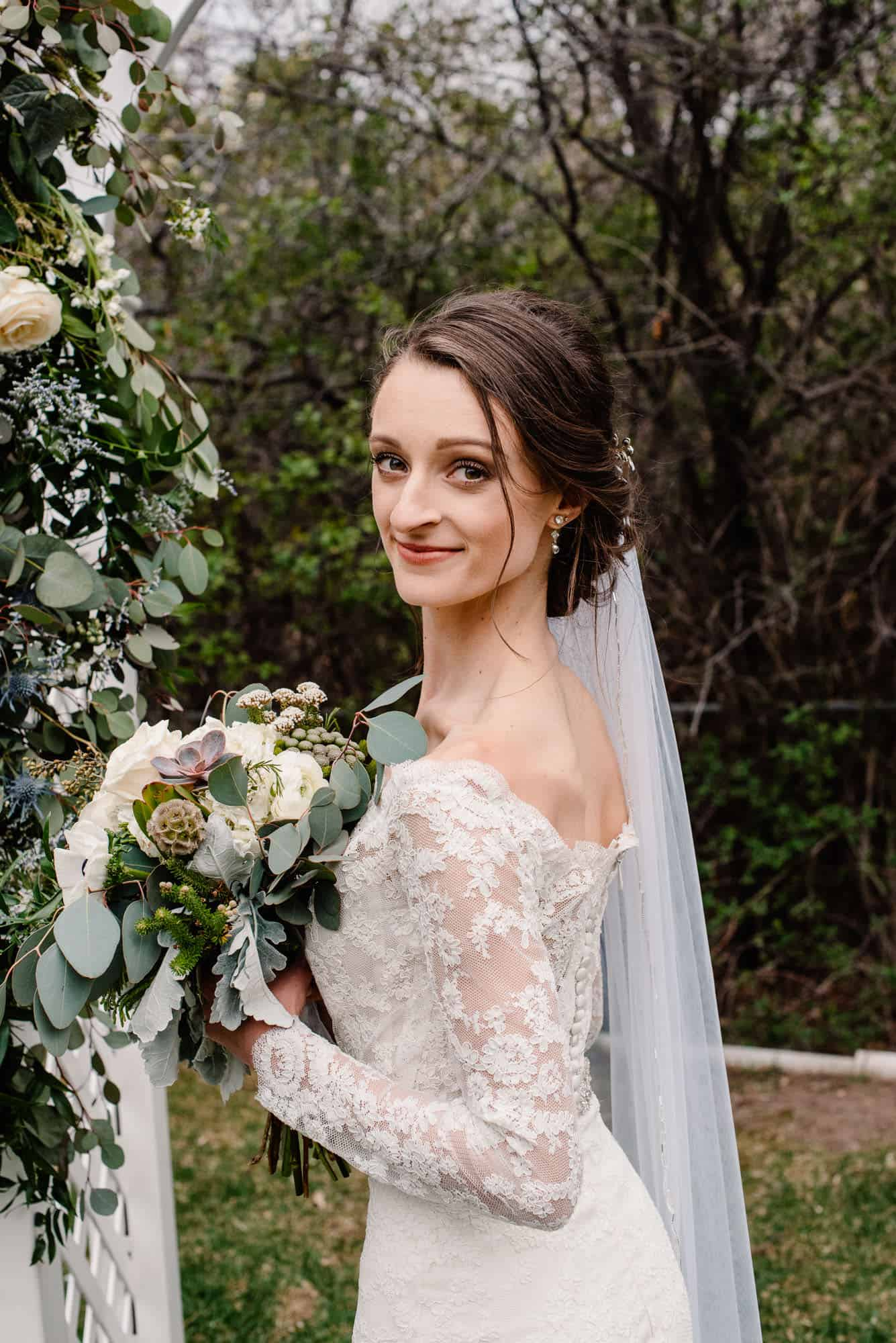 bride who had her make up done on her wedding day turning to look at camera