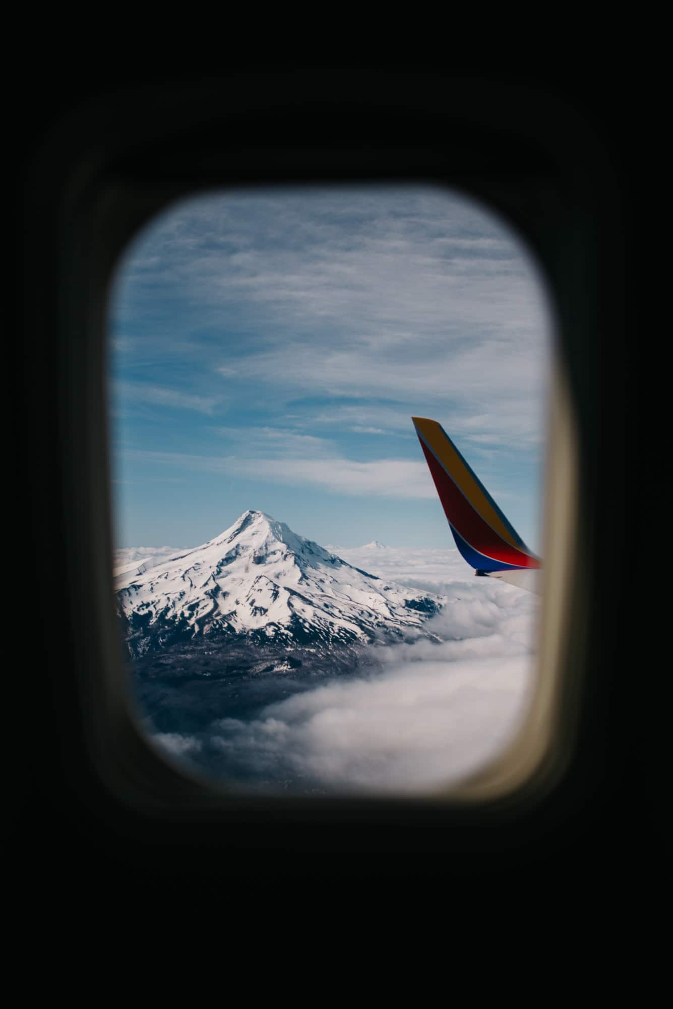 view of an airplane wing and Mount hood In Oregon from a window seat near