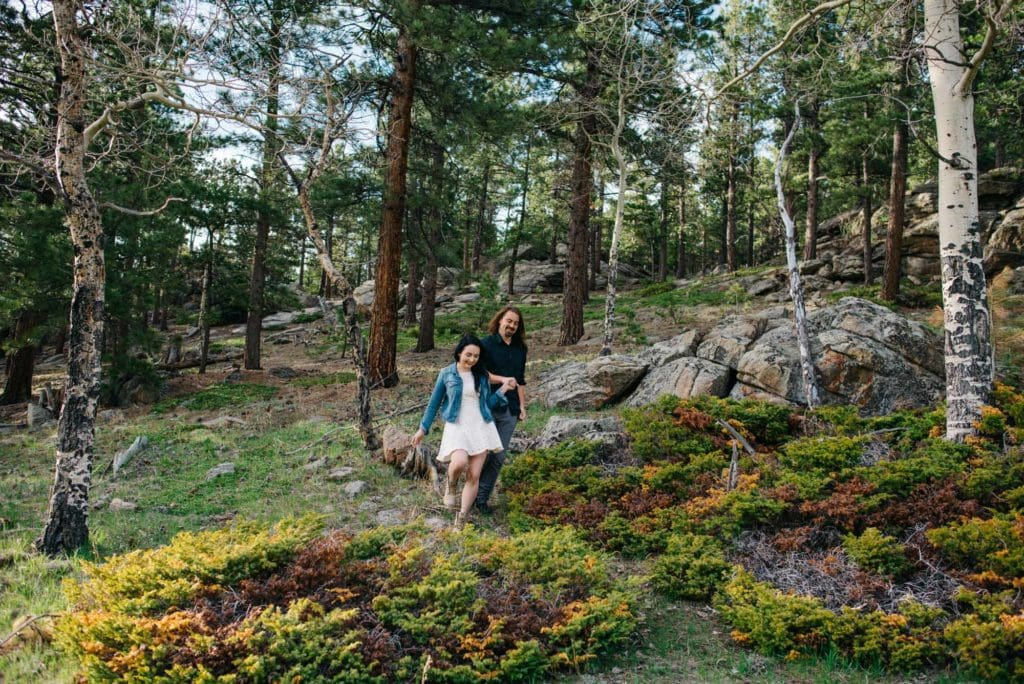 newly weds walking in a mossy field of trees