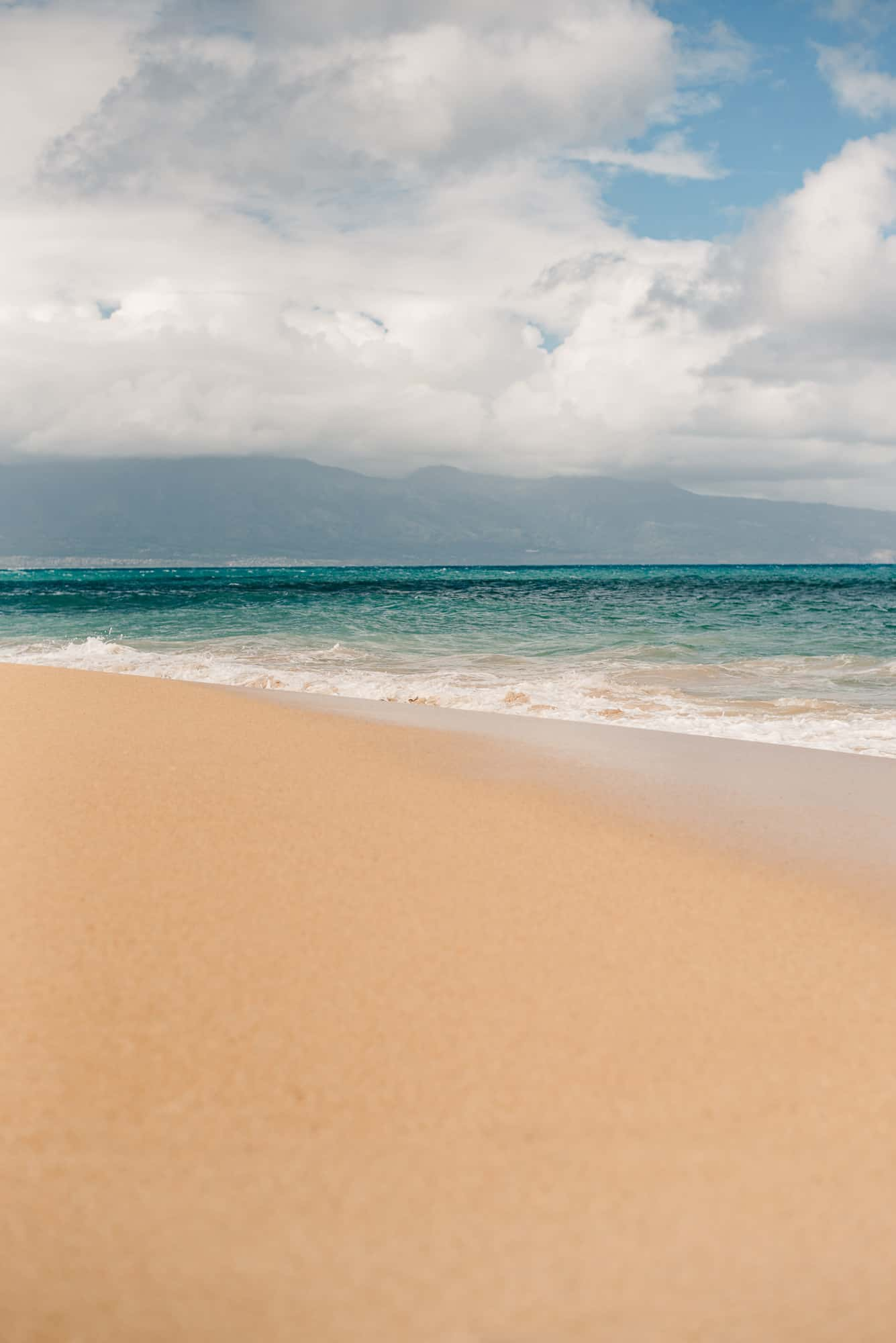 view of the beach in maui on a partly cloudy day