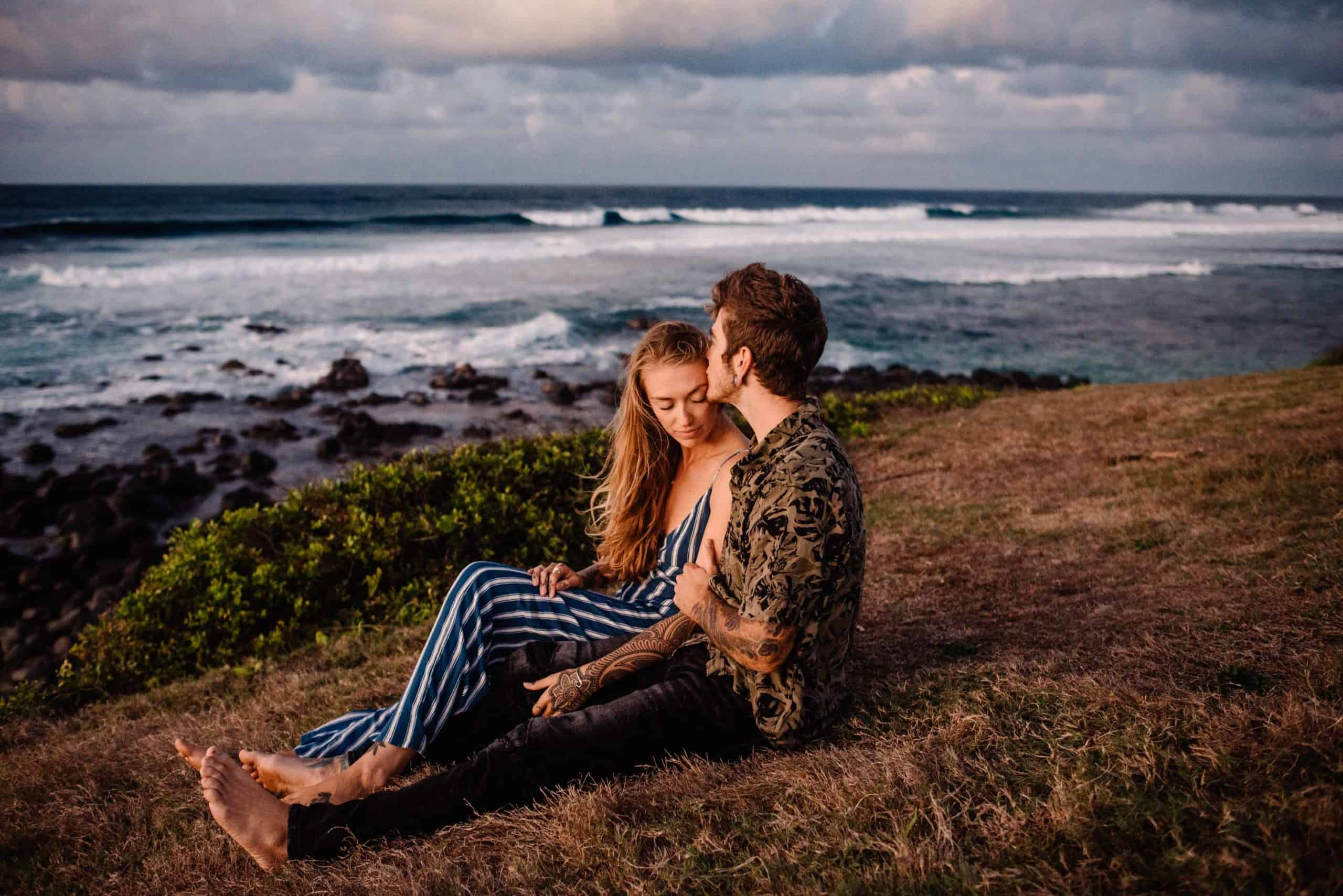 couple snuggling on beach grassy field enjoying snuggles as they do the romantic things to do in maui